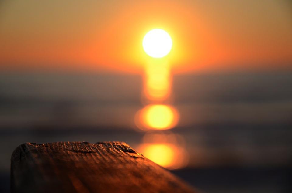 tramonto sfocato sul mare ripreso da un passamano sulle dune di Sabaudia a Latina